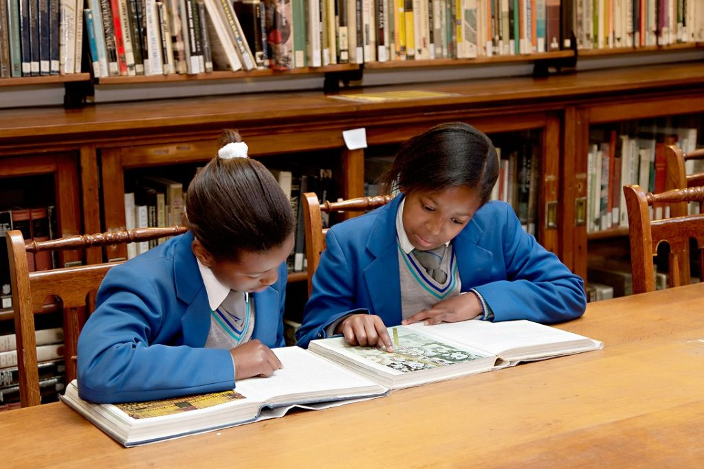 School children reading a book in the school library.